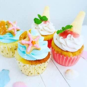 マンゴーと桃のカップケーキを紹介します!  マンゴーのシロップ煮が入った生地に海をイメージした水色のクリームを絞りマンゴーピューレをかけヒトデのアイシングクッキーを飾りました! 桃のカップケーキは、生地・クリーム・ピューレ桃ずくしのカップケーキにミニアイスコーンを飾り、ソフトクリーム風カップケーキにしました!>
